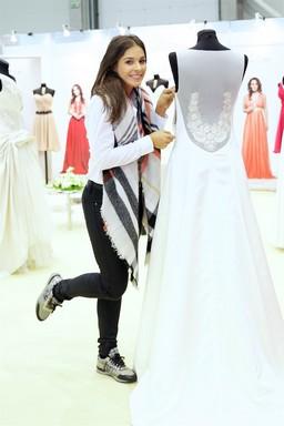 Molnar Andi egy esküvői ruha mellett pózol, Kép: Őszi Esküvő Kiállítás