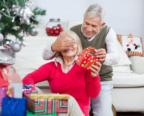 Férfi hátulról befogja a nő szemét, és a karácsonyfa alatt ajándékot ad neki, Kép: tevagyahos.hu