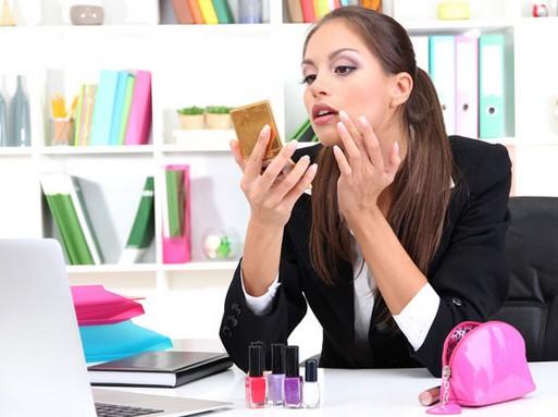 Fiatal nő irodába ül, szépítkezik, előtte laptop és körömlakkok, Kép: sajtóanyag