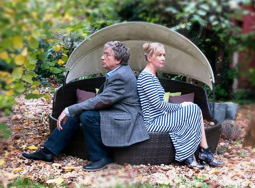 Kern András, a férj és Eszenyi Enikő, mint feleség egymásnak háttal ülnek a kertben