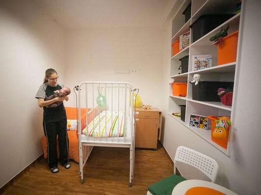 Csinos kórházi szoba gyerekággyal, és egy kinytható felnőtt alvóhellyel, mellette anyuka karjában tartja a gyermkekét, Kép: Csortos Szabolcs/Uni/Pécs