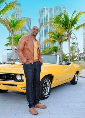 Rosewood, a sorozat főszereplője egy sárga sportkocsi előtt zsebre dugott kézzel, Kép CoolTV