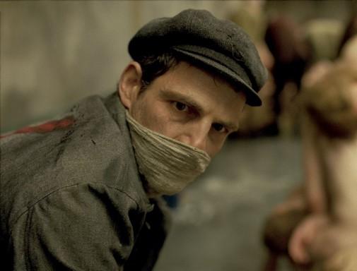 Filmrészlet a Saul fiából, egy férfi hajlott háttól, kendővel száját eltakarva visszanéz