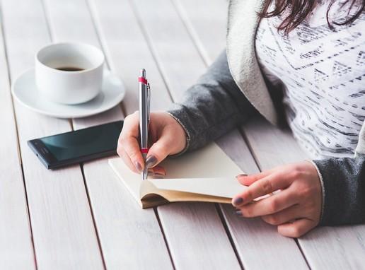 Téli női kéz ír egy kerti asztalon, mellette a telefonja, és egy csésze kávé, Kép: pixabay