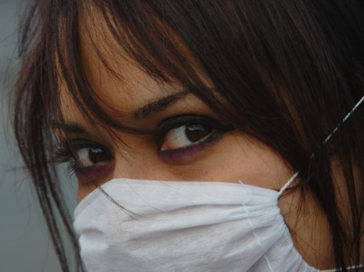 Barna nő közelről, orrán fehér egészségügyi maszk, Kép: flickr