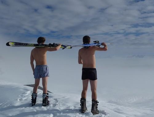 Két férfi hátulról alsónadrágban, sícipőben, vállukon sítalpak, így nézik a havas tájat, Kép: pixabay