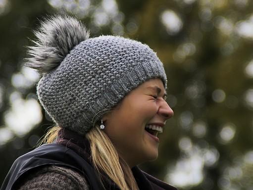 Nagyon nevető lány oldalról, fején szürke téli kötött sapka, Kép: pixabay