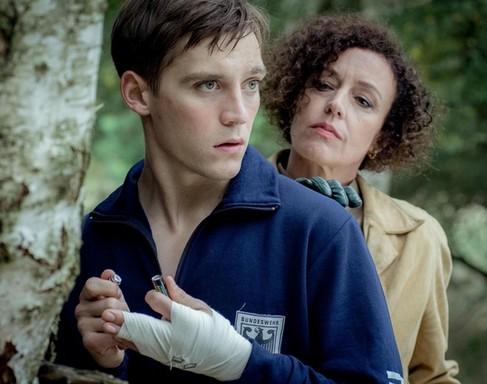 A főszereplő sebesült kézzel, mögötte egy hölgy komoran figyel rá, Kép: RTL