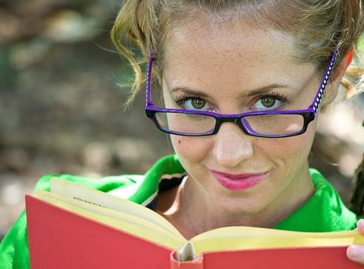 Szemüveges olvasó nő felpillant a köynvből, mosolyog, Kép: pixabay