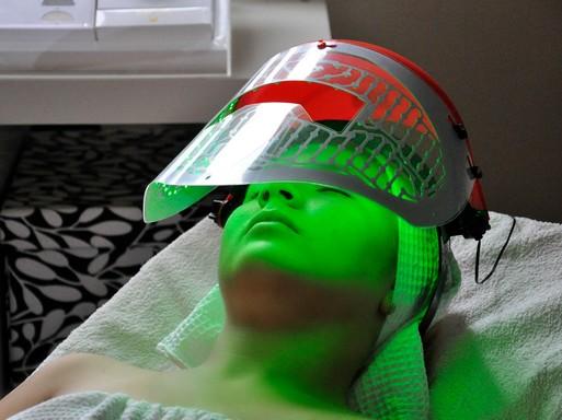 Kozmetikai ágyon fekvő nő, fején egy hokis fejvédőjéhez hasonló, zöld-piros álarc, Kép: Aranyalma Szépségszalon