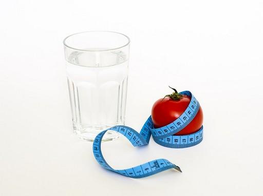 Semleges háttér előtt egy pohár víz, egy paradicsom centivel átkötve, Kép: pixabay