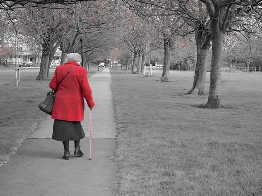 Idős hölgy piros kabátban, bottal, hátulról, Kép: publicdomainpictures