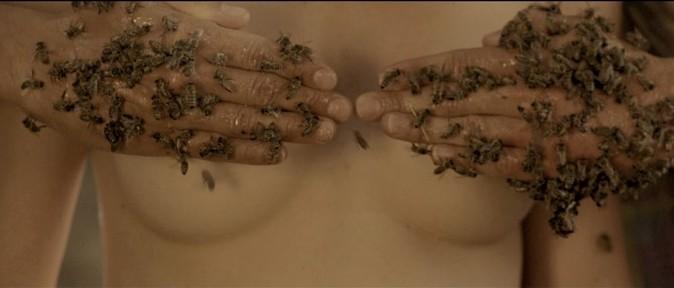 Mézes kezeken méhek, melyek eltakarnak két meztelen női mellett, Kép: ZERO