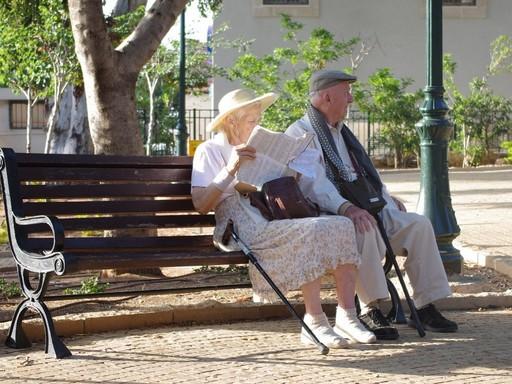 Nyugdíjas idős pár ül egy kerti padon, a hölgy újságot olvas, Kép: pixabay