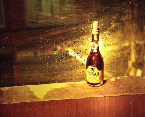 Tokaji borosüveg, mögötte esőcseppes üvegfal, Kép: wikimedia