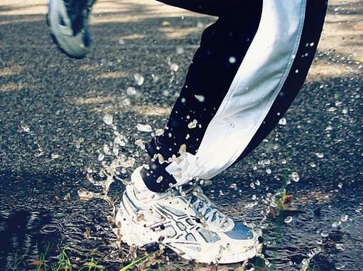 Futó sportoló lábáról közeli felvételi, amikor épp egy pocsolyába csobban, Kép: pixabay