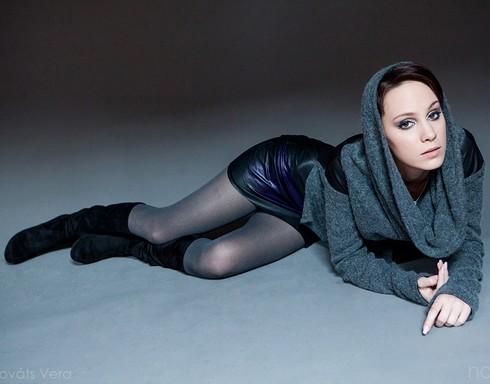 Kováts Vera fekete-sötétszürke ruhában fekszik a szürke padlón, Kép: sajtóanyag