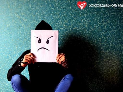 Kék fal előtt törökülésben, fekete sapkában ül valaki, maga elé tart egy fehér papírt, amire egy szomorú arcot festettek, Kép: Boldogságprogram