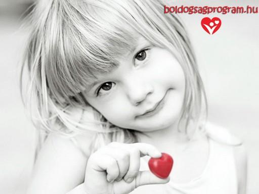 Aranyos szőke kislány kezében egy kis piros szívet tart, Kép: Boldogságprogram