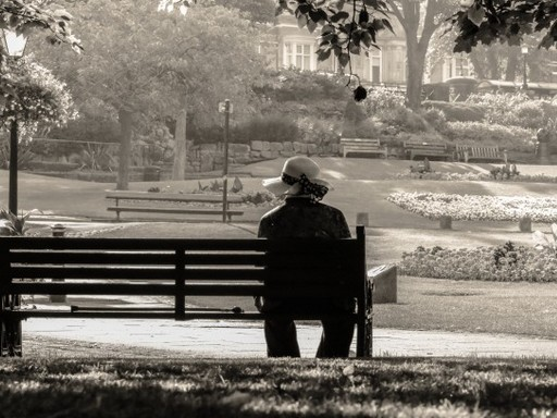 Nő egyedül ül egy köztéri padon, Kép: