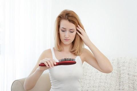 Szép lány szomorúan nézi a kefejét, mert hullik a haja, Kép: Tricovel