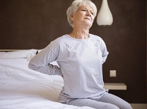Hátfájás, idős nő egyengeti a derekát, Kép: Budai Fájdalomközpont