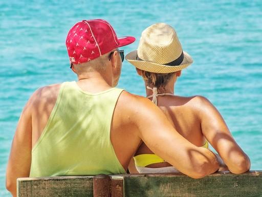Nyaraló nyári pár a tengerparton háttal ül, Kép: pixabay