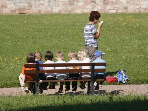 Gyerekek ülnek egy padon az oviban, Kép: pxhere