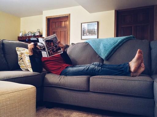 Lakásban, heverőn fekvő férfi újságot olvas, Kép: pexels