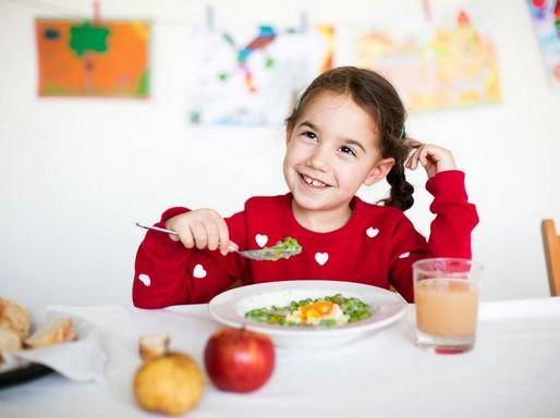 Mosolygós kislány eszik, Kép: Greanpeace Magyarország