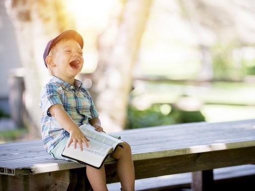 Gyerek kacag egy könyvön, Kép: Budai Egészségközpont